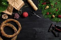 Κάνετε ένα στεφάνι Χριστουγέννων με τα χέρια σας Κομψός κλάδος, στεφάνι Χριστουγέννων και δώρα σε ένα μαύρο ξύλινο υπόβαθρο Στοκ Εικόνες