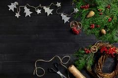 Κάνετε ένα στεφάνι Χριστουγέννων με τα χέρια σας Κομψός κλάδος, στεφάνι Χριστουγέννων και δώρα σε ένα μαύρο ξύλινο υπόβαθρο Στοκ εικόνες με δικαίωμα ελεύθερης χρήσης
