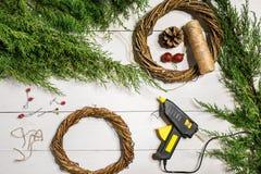 Κάνετε ένα στεφάνι Χριστουγέννων με τα χέρια σας Κομψός κλάδος, στεφάνι Χριστουγέννων και δώρα σε ένα άσπρο ξύλινο υπόβαθρο Στοκ φωτογραφία με δικαίωμα ελεύθερης χρήσης