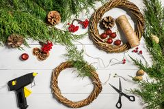 Κάνετε ένα στεφάνι Χριστουγέννων με τα χέρια σας Κομψός κλάδος, στεφάνι Χριστουγέννων και δώρα σε ένα άσπρο ξύλινο υπόβαθρο Στοκ φωτογραφίες με δικαίωμα ελεύθερης χρήσης