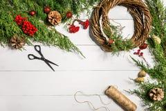 Κάνετε ένα στεφάνι Χριστουγέννων με τα χέρια σας Κομψός κλάδος, στεφάνι Χριστουγέννων και δώρα σε ένα άσπρο ξύλινο υπόβαθρο Στοκ Εικόνα