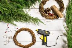 Κάνετε ένα στεφάνι Χριστουγέννων με τα χέρια σας Κομψός κλάδος, στεφάνι Χριστουγέννων και δώρα σε ένα άσπρο ξύλινο υπόβαθρο Στοκ εικόνες με δικαίωμα ελεύθερης χρήσης