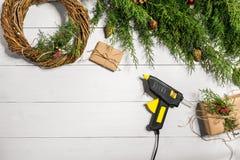 Κάνετε ένα στεφάνι Χριστουγέννων με τα χέρια σας Κομψός κλάδος, στεφάνι Χριστουγέννων και δώρα σε ένα άσπρο ξύλινο υπόβαθρο Στοκ εικόνα με δικαίωμα ελεύθερης χρήσης