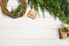 Κάνετε ένα στεφάνι Χριστουγέννων με τα χέρια σας Κομψός κλάδος, στεφάνι Χριστουγέννων και δώρα σε ένα άσπρο ξύλινο υπόβαθρο Στοκ Εικόνες