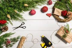 Κάνετε ένα στεφάνι Χριστουγέννων με τα χέρια σας Κομψός κλάδος, στεφάνι Χριστουγέννων και δώρα σε ένα άσπρο ξύλινο υπόβαθρο Στοκ Φωτογραφίες