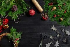 Κάνετε ένα στεφάνι Χριστουγέννων με τα χέρια σας Κομψός κλάδος, στεφάνι Χριστουγέννων και δώρα σε ένα μαύρο ξύλινο υπόβαθρο Στοκ Φωτογραφίες