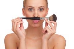 Κάνετε ένα mustache με τη βούρτσα makeup. Στοκ φωτογραφία με δικαίωμα ελεύθερης χρήσης