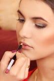 Κάνετε στο νέο κορίτσι μια σύνθεση, makeup χείλια Στοκ Εικόνες