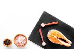 Κάνετε τα αλμυρά ψάρια Ακατέργαστη μπριζόλα σολομών στον τέμνοντα πίνακα κοντά στο κύπελλο με το άλας και πιπέρι στο άσπρο αντίγρ Στοκ φωτογραφίες με δικαίωμα ελεύθερης χρήσης