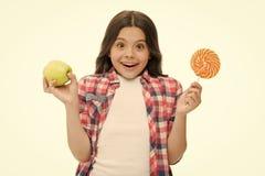 Κάνετε τη σωστή επιλογή Μπορέστε να γλυκάνετε το γλυκό γούστο μας κάνει ευτυχησμένους Το κορίτσι κρατά το γλυκά lollipop και το μ στοκ εικόνες