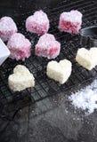 Κάνοντας το αυστραλιανό ύφος τη ρόδινη καρδιά να διαμορφώσει τα μικρά κέικ lamington - κάθετος στενός επάνω Στοκ Εικόνες