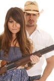 Κάουμποϋ πίσω από τη γυναίκα με το πυροβόλο όπλο σοβαρό Στοκ Εικόνα