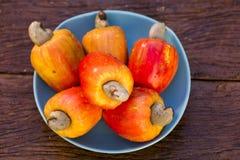Κάποια φρούτα των δυτικών ανακαρδίων πέρα από μια ξύλινη επιφάνεια στοκ εικόνες