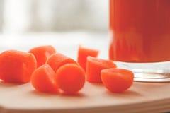 Κάποιοι μικρά τεμαχισμένα καρότα και φωτεινός πορτοκαλής χυμός καρότων στο ξύλινο υπόβαθρο στοκ φωτογραφία με δικαίωμα ελεύθερης χρήσης