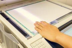 Κάποιος αντιγράφει το έγγραφο στη μηχανή αντιγράφων το μη-αγγλικό κείμενο σημαίνει Στοκ φωτογραφία με δικαίωμα ελεύθερης χρήσης
