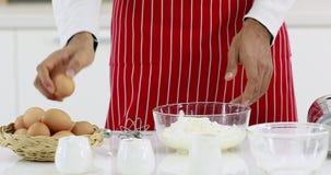 Κάποιος που αναμιγνύει το αλεύρι, γάλα, αυγό στο κύπελλο γυαλιού απόθεμα βίντεο