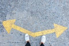 Κάποιος που φορά τα πάνινα παπούτσια που επιλέγουν το α με τις επιλογές βελών κατεύθυνσης αριστερά ή δεξιά στοκ φωτογραφίες
