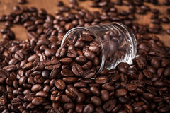Κάποιο φασόλι καφέ στο γυαλί του σωρού φασολιών καφέ στον ξύλινο πίνακα Στοκ Φωτογραφίες