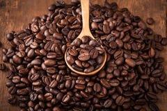 Κάποιο φασόλι καφέ στο κουτάλι του σωρού φασολιών καφέ στον ξύλινο πίνακα Στοκ φωτογραφίες με δικαίωμα ελεύθερης χρήσης