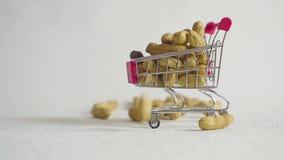 Κάρρο αγορών από την υπεραγορά που γεμίζουν με τα καρύδια φυστικιών πτώση φυστικιών στο κάρρο υπεραγορών φιλμ μικρού μήκους