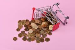 Κάρρο αγορών και διεσπαρμένα νομίσματα Στοκ φωτογραφία με δικαίωμα ελεύθερης χρήσης