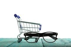 Κάρρο αγορών με τα γυαλιά ανάγνωσης που απομονώνονται σε ένα λευκό στοκ εικόνες