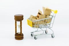 Κάρρο αγορών με τα νομίσματα μέσα στο κιβώτιο και την κλεψύδρα για τη λιανική επιχείρηση Χρήση εικόνας για να ψωνίσει, θέση μάρκε Στοκ Φωτογραφίες