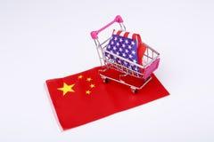 Κάρρο αγορών με την ΑΜΕΡΙΚΑΝΙΚΗ σημαία στη σημαία της Κίνας Στοκ Φωτογραφίες