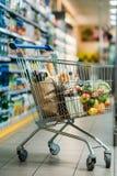 κάρρο αγορών με τις αγορές στην υπεραγορά Στοκ Φωτογραφίες