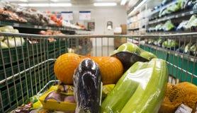 Κάρρο αγορών που γεμίζουν επάνω με τα τρόφιμα μεταξύ των ραφιών μιας υπεραγοράς Άποψη από την άποψη πελατών Στοκ εικόνες με δικαίωμα ελεύθερης χρήσης