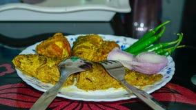 κάρρυ ψαριών, κρεμμύδι, τσίλι σε ένα πιάτο στο να δειπνήσει πίνακα στοκ εικόνα