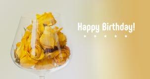 κάρτα γενεθλίων ευτυχής Ξηρός αυξήθηκε λουλούδια στο γυαλί κρασιού, μπεζ υπόβαθρο κλίσης κίτρινη μακρο άποψη πετάλων, διάστημα αν Στοκ Εικόνες