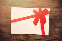 Κάρτα δώρων στην ξύλινη κάρτα δώρων υποβάθρου ροζ άσπρη που διακοσμείται με το κόκκινο τόξο κορδελλών στη Χαρούμενα Χριστούγεννα  στοκ εικόνα με δικαίωμα ελεύθερης χρήσης