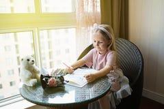 Κάρτα ζωγραφικής κορών παιδιών για το mom Συνεδρίαση κοριτσιών στο σπίτι στον πίνακα, έπειτα να βρεθεί ρόδινο λουλούδι για τη μητ στοκ εικόνα με δικαίωμα ελεύθερης χρήσης