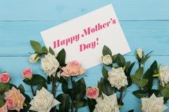 Κάρτα ημέρας μητέρων και όμορφα τριαντάφυλλα στο μπλε ξύλινο υπόβαθρο Στοκ Φωτογραφίες