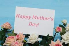 Κάρτα ημέρας μητέρων και όμορφα τριαντάφυλλα στο μπλε ξύλινο υπόβαθρο Στοκ Εικόνα
