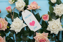 Κάρτα ημέρας μητέρων και όμορφα τριαντάφυλλα στο μπλε ξύλινο υπόβαθρο Στοκ φωτογραφία με δικαίωμα ελεύθερης χρήσης