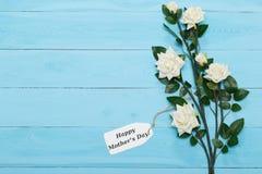Κάρτα ημέρας μητέρων και όμορφα τριαντάφυλλα στο μπλε ξύλινο υπόβαθρο Στοκ Εικόνες