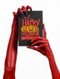 Κάρτα και ευτυχές θέμα αποκριών: κόκκινο χέρι διαβόλων με τα μαύρα καρφιά που κρατούν μια κάρτα εγγράφου με τις λέξεις ευτυχείς α Στοκ Εικόνες