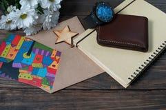 Κάρτα και λουλούδια δώρων στο ξύλινο υπόβαθρο στοκ εικόνες