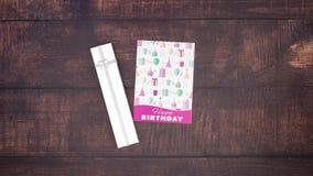 Κάρτα και παρόν γενεθλίων στο ξύλινο υπόβαθρο φιλμ μικρού μήκους