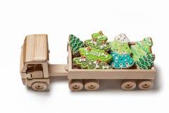 Κάρτα με το νέα έτος και τα Χριστούγεννα Φορτηγό παιχνιδιών με το μελόψωμο Στοκ Φωτογραφίες
