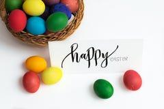 Κάρτα Πάσχας με τα ζωηρόχρωμα αυγά Πάσχας σε ένα καλάθι και μια καλλιγραφική επιγραφή ευτυχές Πάσχα Στοκ Φωτογραφία