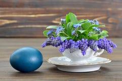 Κάρτα Πάσχας με τα λουλούδια αυγών Πάσχας και άνοιξη στο φλυτζάνι τσαγιού Στοκ φωτογραφία με δικαίωμα ελεύθερης χρήσης