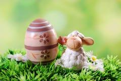 Κάρτα Πάσχας με το χαριτωμένο αρνί και αυγό στη χλόη Στοκ Εικόνες