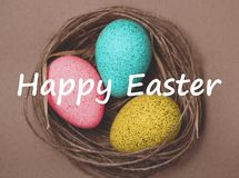 κάρτα Πάσχα Χρωματισμένα αυγά Πάσχας στη φωλιά, καφετί υπόβαθρο Σύμβολο άνοιξη, χριστιανισμός θρησκείας Αναδρομική κάρτα δώρων ύφ Στοκ Εικόνα