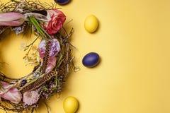 κάρτα Πάσχα Χρωματισμένα αυγά Πάσχας στη φωλιά στο κίτρινο υπόβαθρο Στοκ Φωτογραφία