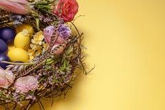 κάρτα Πάσχα Χρωματισμένα αυγά Πάσχας στη φωλιά στο κίτρινο υπόβαθρο Στοκ εικόνα με δικαίωμα ελεύθερης χρήσης