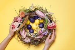 κάρτα Πάσχα Χρωματισμένα αυγά Πάσχας στη φωλιά στο κίτρινο υπόβαθρο Στοκ Εικόνες