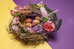 κάρτα Πάσχα Χρωματισμένα αυγά Πάσχας στη φωλιά στο κίτρινο υπόβαθρο Στοκ Εικόνα
